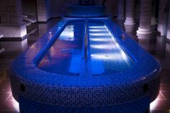 A luxury pillared spa hall with the illuminated plunge pool in the centre. An empty beautiful blue-tiled spa pool of the deluxe ho. Tel. Wall columns sauna stock photography