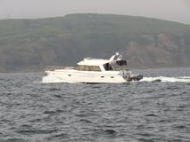 Luxury pleasure motor boat sailing along the steep green coast stock images