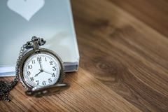 Luxury pocket watch over the book on the wooden table with copy space Stock Photography