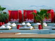 Luxury poolside. With canopy beds, palm trees and the Atlas mountain at the back Royalty Free Stock Photo