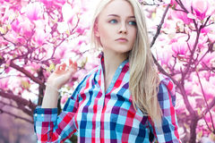 Luxury portrait of serious young blonde girl with flowers Stock Photo