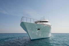 Luxury private motor yacht sailing at sea. A luxury private motor yacht under way on tropical sea with bow wave Stock Photos