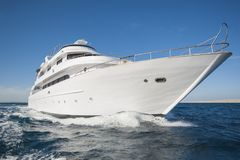 Luxury private motor yacht sailing at sea. A luxury private motor yacht under way on tropical sea with bow wave Stock Image