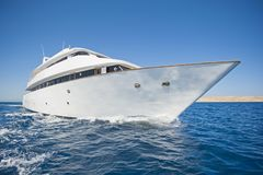 Luxury private motor yacht sailing at sea. A luxury private motor yacht under way on tropical sea with bow wave Royalty Free Stock Images