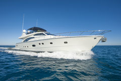 Luxury private motor yacht sailing at sea. A luxury private motor yacht under way on tropical sea with bow wave Royalty Free Stock Photos