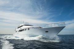 Luxury private motor yacht sailing at sea. A luxury private motor yacht under way on tropical sea with bow wave Royalty Free Stock Image