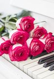 Luxury red roses on a piano. Bouquet of red roses and piano. Keys Stock Photo