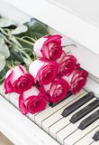 Luxury red roses on a piano. Bouquet of red roses and piano. Keys royalty free stock photo