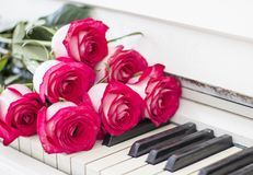 Luxury red roses on a piano. Bouquet of red roses and piano stock photography