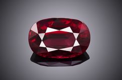 Luxury red transparent sparkling gemstone shape oval cut ruby isolated on grey background royalty free stock image