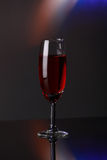 Luxury red wine in champagne flute. On grey background Stock Photo