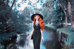 Luxury redhead girl in black retro dress on nature. Beautiful vintage woman with red lips. Stylish lady in retro hat. Fashion