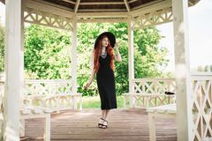 Luxury Redhead Girl In Black Retro Dress In Arbor. Beautiful Vintage Woman With Red Lips. Stylish Lady In Retro Hat. Fashion Royalty Free Stock Images