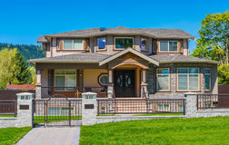 Luxury residential house. With iron fence and green lawn in front Royalty Free Stock Image