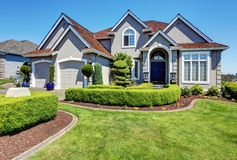 Luxury residential house with perfectly kept front garden. Luxury residential house with perfectly kept front garden and blue sky background. Northwest, USA stock photos