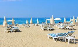 Luxury resort beach with umbrellas and sun beds on white sand near blue sea on bright sunny day Royalty Free Stock Photos