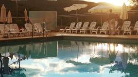 Luxury resort evening time. Pool worker folding sun umbrellas stock video