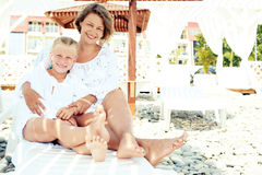 Luxury resort happy family relaxing . Mother and daughter lying down on deckchair of beach resort . Summer vacation idea Royalty Free Stock Photos