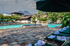 Luxury Resort Pool - Antigua, Guatemala. Old world elegance at a resort pool with a central fountain and a row of green lounge chairs. The Guatemalan mountains Royalty Free Stock Photography