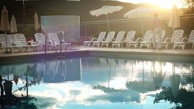 Luxury resort pool in the evening time - worker folds down the umbrellas. Luxury resort pool in the evening time - hotel's staff worker folds down the umbrellas stock video