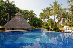 Luxury resort swimming pool. Blue swimming pool and thatched roof pool house at a tropical luxury resort in Puerto Vallarta, Mexico Royalty Free Stock Photos