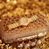 Luxury rich golden wristwatch and purse, on golden sequins - spa Stock Photography