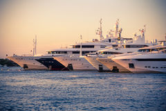 Luxury, rich Yachts moored in a harbor of Porto Cervo. Luxury Yachts moored in a harbor of Porto Cervo on the early sunset, Sardinia, Italy Royalty Free Stock Photos
