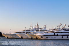 Luxury, rich Yachts moored in a harbor of Porto Cervo. Luxury Yachts moored in a harbor of Porto Cervo on the early sunset, Sardinia, Italy Stock Images
