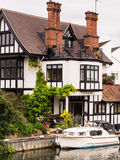 Luxury River Bank House. Luxury house at Marlow Lock on the river Thames, with a boat moored outside. Buckinghamshire, England royalty free stock images