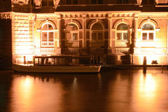 Luxury river boat and hotel. Long exposure night shot of a five star luxury hotel and river cruise boat on the side of a canal with bright reflections in the stock photography