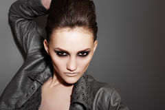 Luxury rock woman with fashion evening make-up. Luxury rock woman in leather jacket with fashion evening make-up near to the dark gray wall Royalty Free Stock Photography