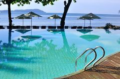 Luxury and rustic swimming pool by the sea. A luxury and rustic swimming pool surrounded by the sea at the tropical Langkawi Island . At the background , a few Stock Image