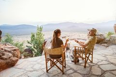 Luxury safari vacation. Romantic couple on safari vacation sitting outdoor at lodge enjoying stunning views over national park with glass of sundowner wine royalty free stock photos