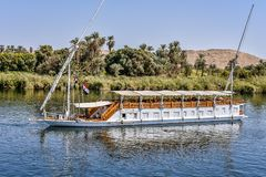 Small cruise boat with two sails on the Nile. Luxury sailing boat for turists on the river Nile, people sitting on the upper deck, Egypt, October 23, 2018 stock photo