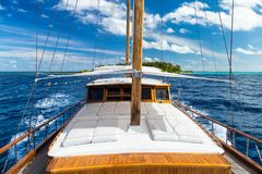 Luxury sailing boat yacht in front of tropical paradise maldives island resort with coral reef and blue ocean water tourism stock images