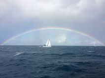 Luxury sailing yacht under a rainbow on the open sea Stock Photo