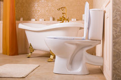 Luxury sanitary equipment with gold elements. Rich bath with gold roll-tops in the form of animal paws, golden faucet and toilet in the bathroom Royalty Free Stock Photography