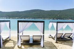 Luxury sea resort in Bodrum ,Turkey. Luxury hotel Beach area with empty  sunbeds with white curtains -summer holiday  Concept Royalty Free Stock Images