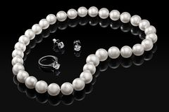 Luxury set white pearl necklace and jewelry with diamonds in ring and earrings on a black background with glossy reflection Stock Images