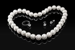 Luxury set white pearl necklace and jewelry with diamonds in ring and earrings on a black background Stock Photos