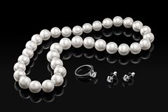 Luxury set white pearl necklace and jewelry with diamonds in ring and earrings on a black background Stock Images