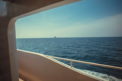 Luxury ship yacht window with a relaxing seascape ocean and blue sky view. Royalty Free Stock Photo