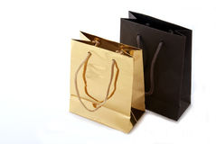 Luxury shopping bags. Two luxury shopping bags, gold and brown on white background royalty free stock images