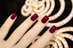 Luxury short manicure Burgundy. Royalty Free Stock Images