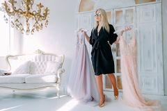 Luxury showroom personal fashion assistant. Luxury showroom. Rich modern interior. Personal fashion assistant performing elegant evening gowns stock image