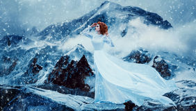 Luxury snow queen. Stands on top of the snow-covered mountains and looks into the distance,fashionable toning,creative computer colorsn Stock Photography