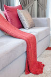 Luxury sofa with pillows and red blanket in living room Stock Photography