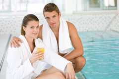 Luxury spa - young sportive couple relax at pool royalty free stock photos