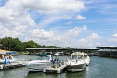Luxury speedboats fueling up at gas pump at marina on lake with docks and boats behind under beautiful blue cloudy sky stock photo