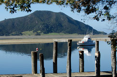 Luxury sport fishing boat. Against Mt Camel(Houhora Mountain) in Pukenui wharf, New Zealand royalty free stock images